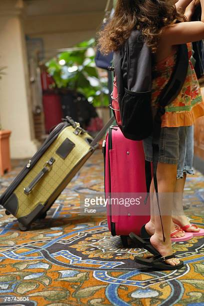 Two Girls with Suitcases in Hotel Lobby