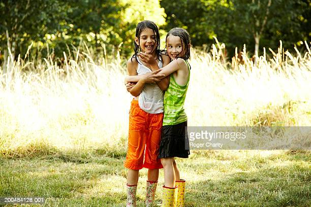 Two girls (6-8) with wet clothes hugging and laughing, outdoors