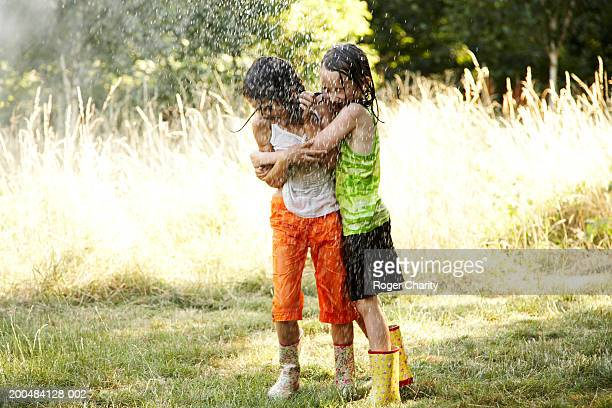 Two girls (6-8) with wet clothes hugging and laughing under sprinkler