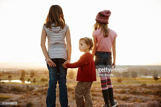 Two girls with younger boy looking at sunset.