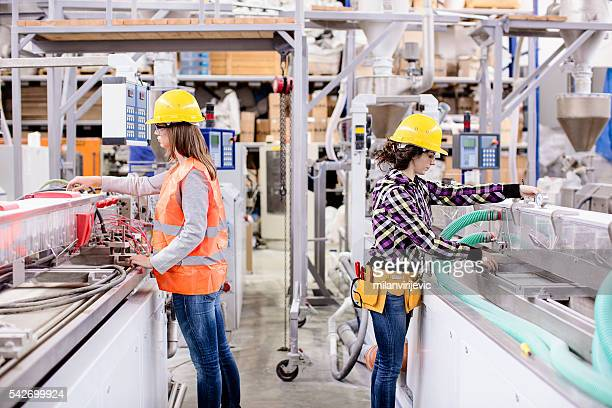 two girls working in a factory - maken stockfoto's en -beelden