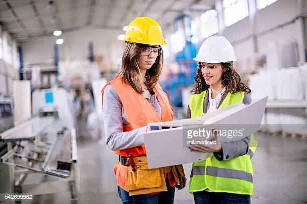 Two girls working together in factory