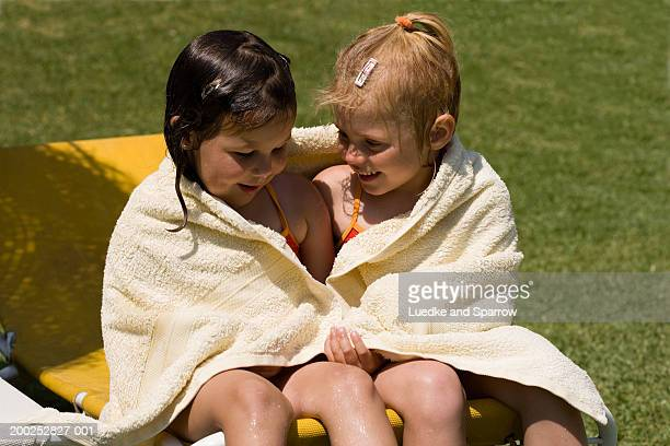 two girls (4-6) wrapped in towel on sun lounger, smiling - only girls stock pictures, royalty-free photos & images