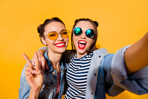 Two glad positive grinning lady stand in glasses spectacles street style stylish trendy cool casual denim jeans clothes isolated on yellow background in take picture on cellular make hollywood smile 1092715214