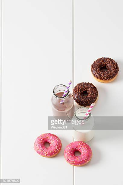 Two glass bottles of milk and cocoa and four doughnuts with different icings on white ground