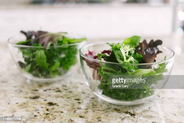 two glass bowls filled with salad greens on kitchen counter - green salad stock pictures, royalty-free photos & images