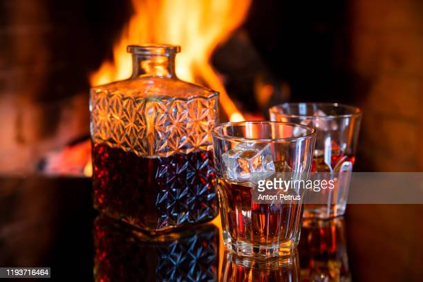 two glasses and a of whiskey near the fireplace. - warming up stock pictures, royalty-free photos & images