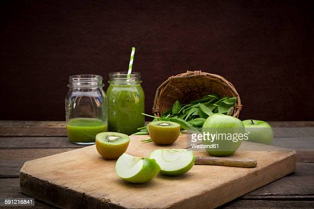 Two glasses of apple kiwi spinach smoothie and ingredients