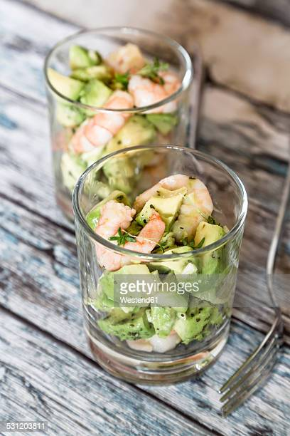 Two glasses of avocado shrimp salad on wood