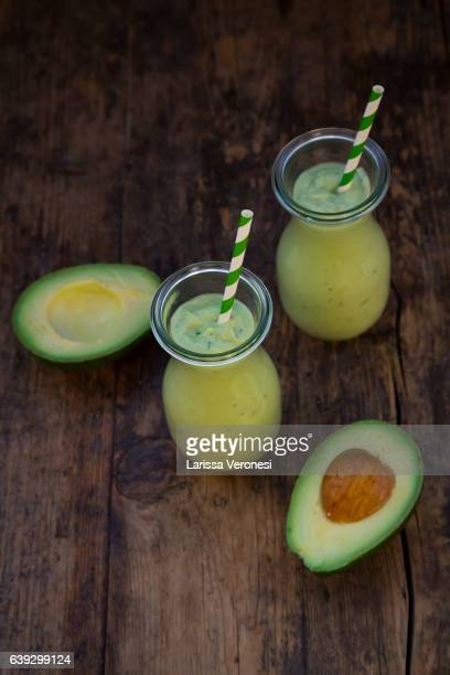two glasses of avocado smoothie and avocados on wood