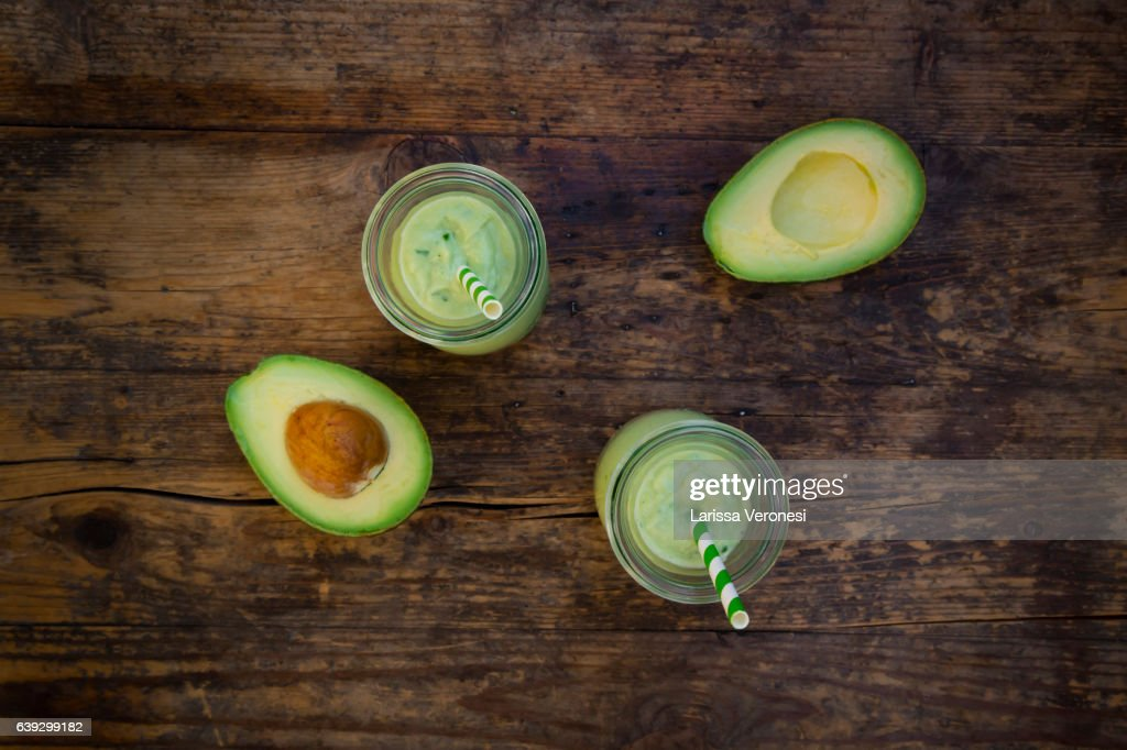 two glasses of avocado smoothie and avocados on wood : Stock-Foto