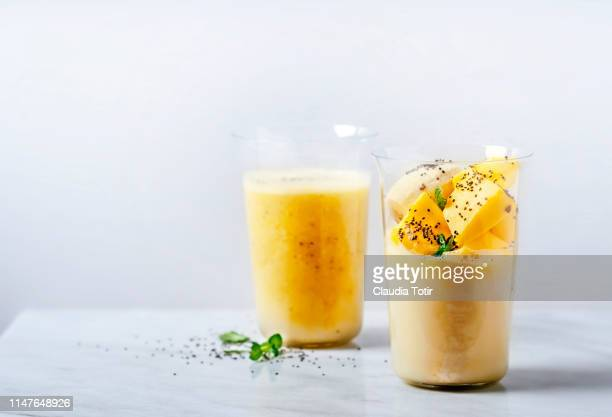 two glasses of banana and mango smoothie on white background - smoothie stockfoto's en -beelden