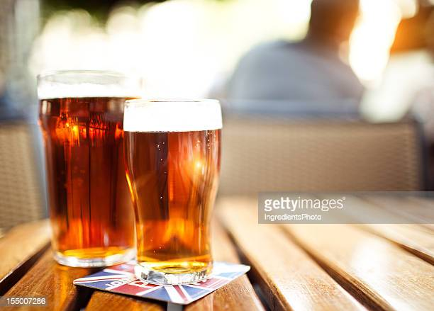 Two glasses of beer on the wooden table.