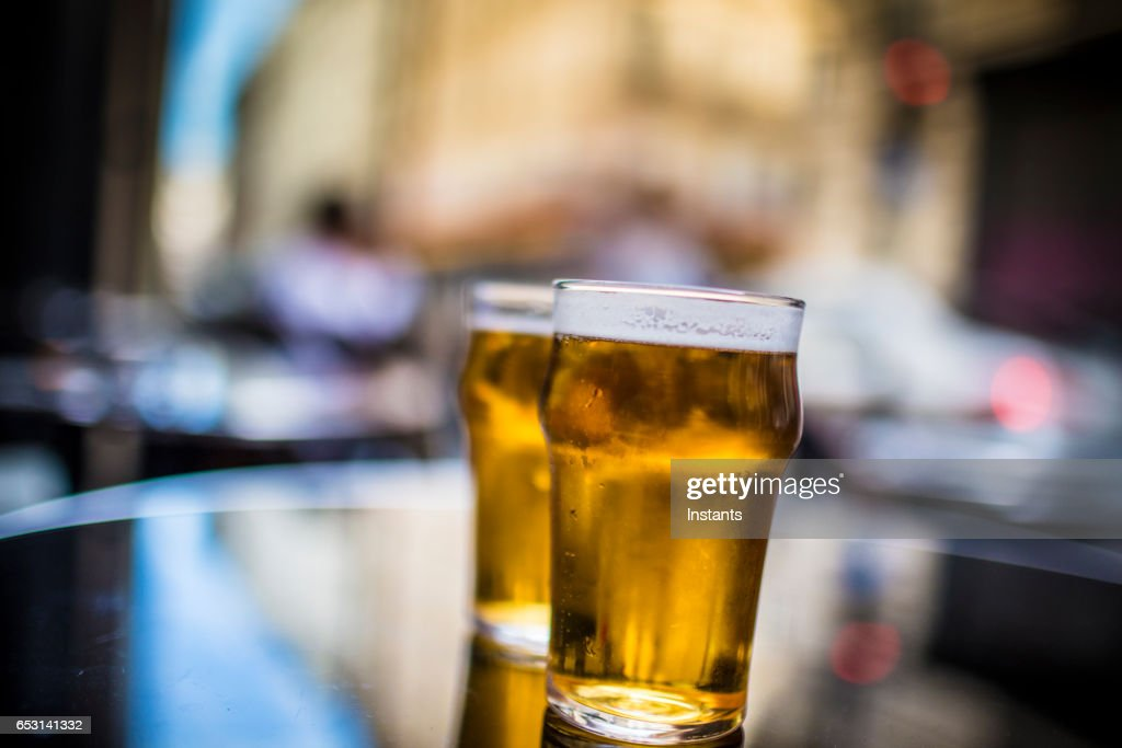 Two glasses of blonde beer on a table, shot on a Parisian cafe bar sidewalk. : Stock Photo