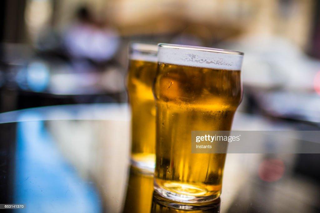 Twee glazen blond bier op een tafel, geschoten op de stoep van een Parijse café bar. : Stockfoto