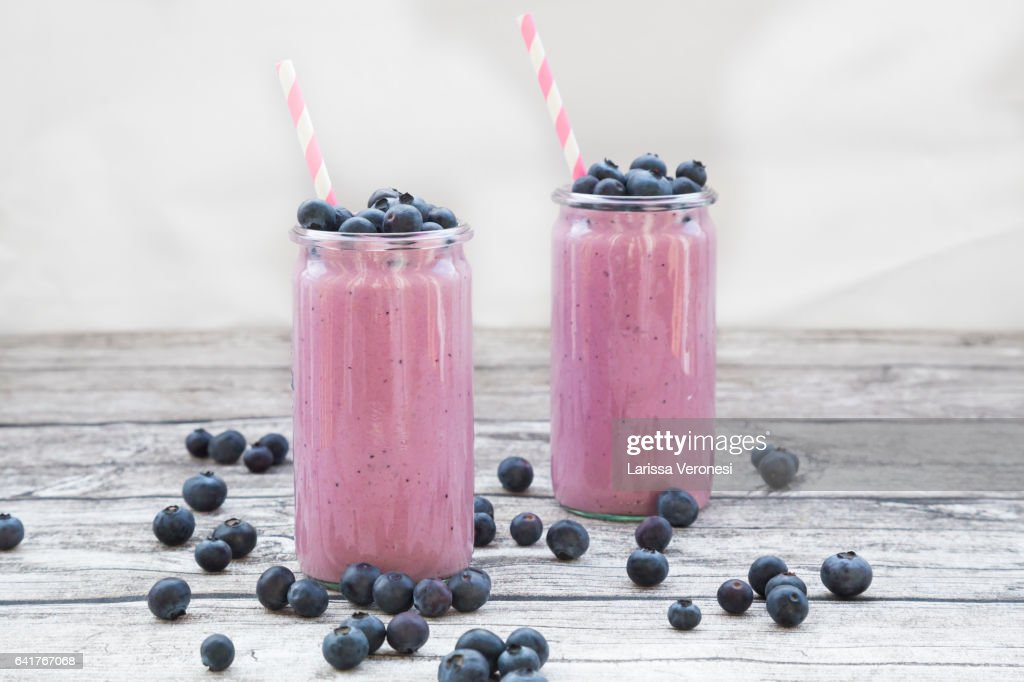 two glasses of blueberry smoothie and blueberries on wood : Stock Photo