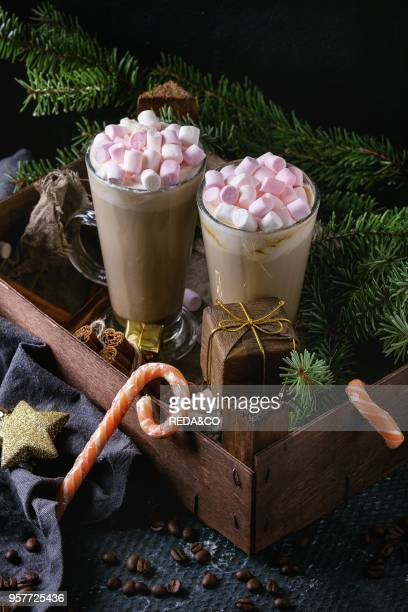 Two glasses of cafe latte with pink marshmallow standing in wooden box with Christmas decor candies spices coffee beans and fir tree over dark...