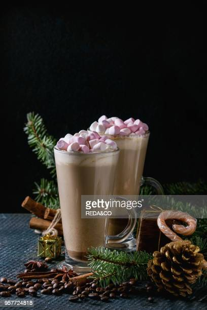 Two glasses of cafe latte with pink marshmallow with Christmas decor candies spices coffee beans and fir tree over dark texture background Top view...