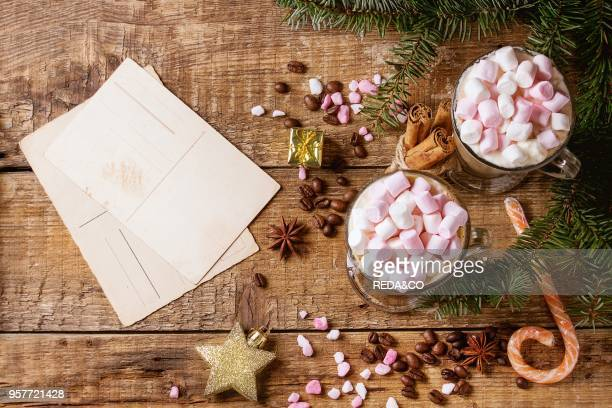 Two glasses of cafe latte with pink marshmallow with empty greeting card Christmas decor pink sugar candy spices coffee beans and fir tree over...