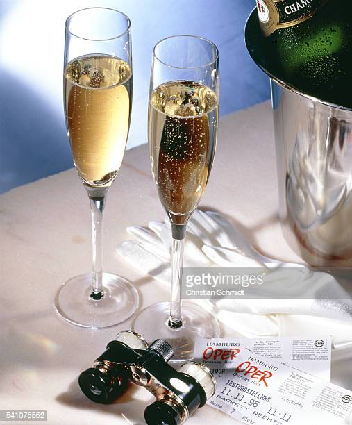 Two glasses of champagne, opera-glass and tickets