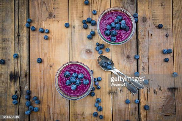 two glasses of chia blueberry pudding and two tea spoons on wood - ティースプーン ストックフォトと画像