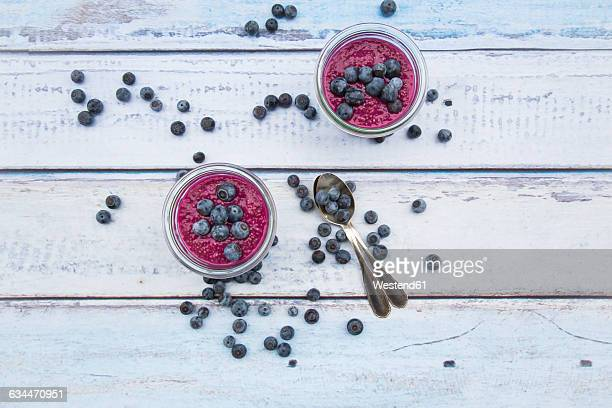 Two glasses of chia blueberry pudding and two tea spoons on wood