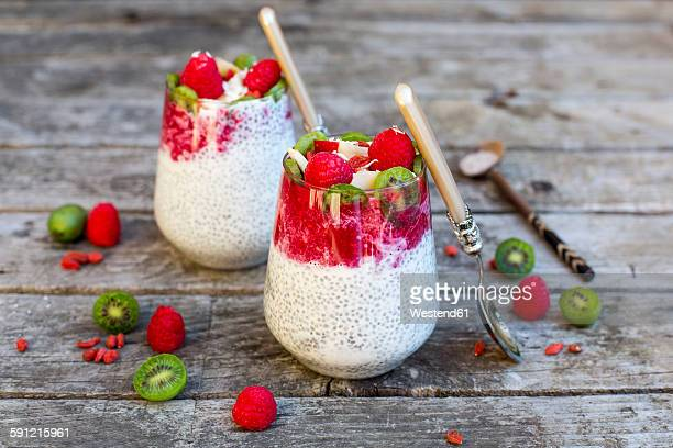 Two glasses of chia pudding with cocos, raspberry sauce and several fruits