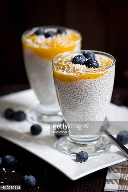 Two glasses of chia pudding with mango banana mush, blueberries and coconut flakes