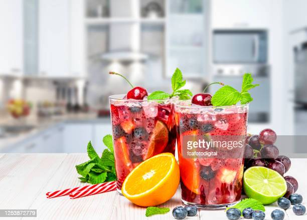 two glasses of cold refreshing sangria with fruits on kitchen counter - sangria stock pictures, royalty-free photos & images