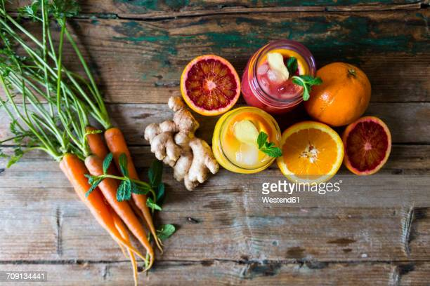 Two glasses of different orange juices, oranges, carrots, mint leaves and ginger