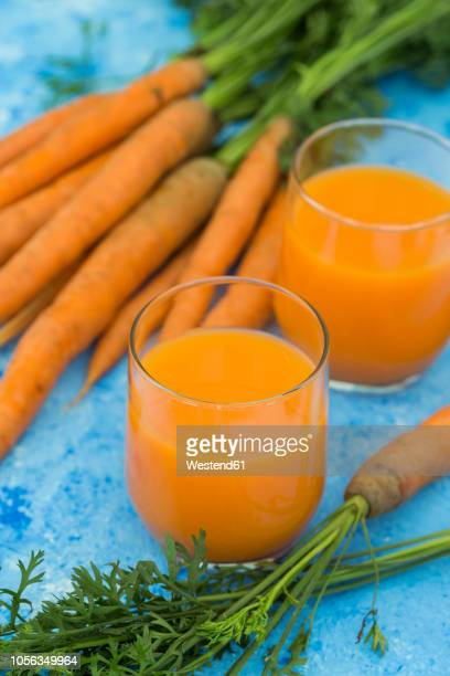 Two glasses of fresh carrot juice and  carrots on light blue ground