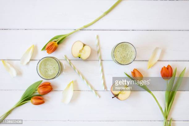 Two glasses of green smoothie, sliced apple, chicory and tulips on white ground