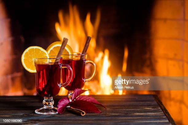 Two glasses of hot mulled wine with spices on wooden table against fireplace