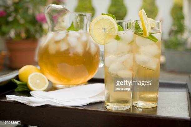Two glasses of iced tea with lemons outdoors