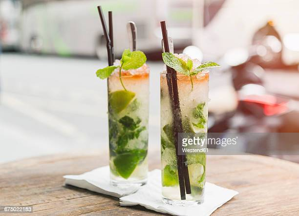 two glasses of mojito on table of sidewalk cafe - mojito stock photos and pictures