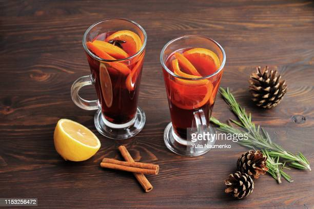 two glasses of mulled wine with cinnamon, oranges, fir cones and rosemary on a brown background. - warme dranken stockfoto's en -beelden
