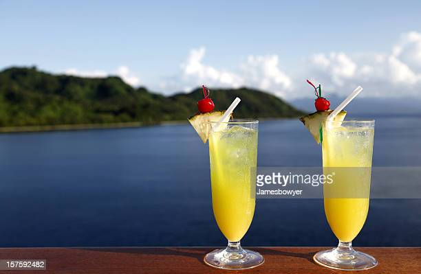 Two glasses of orange cocktail drinks by the water