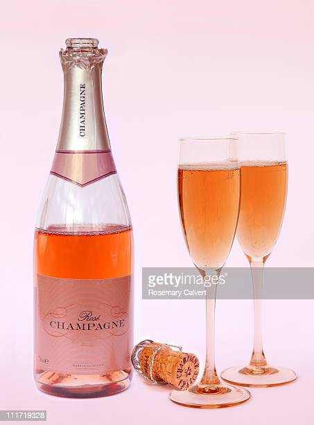 Two glasses of pink champagne poured from bottle.