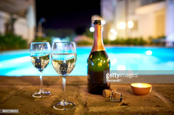 two glasses of prosecco a the poolside by night - prosecco stock pictures, royalty-free photos & images