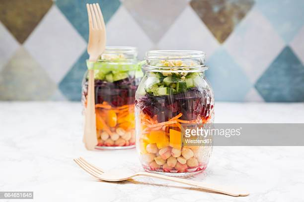 Two glasses of rainbow salad with chick-peas and different vegetables