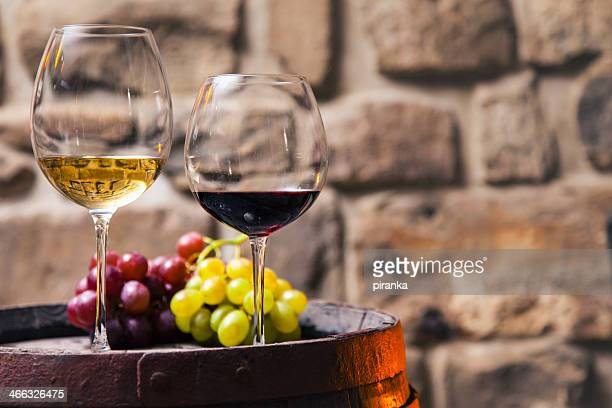 two glasses of red and white wine in the cellar with grapes - white wine stock pictures, royalty-free photos & images