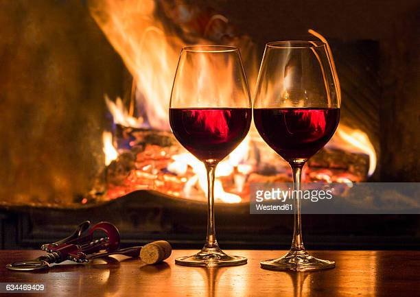 Two glasses of red wine in front of a fireplace