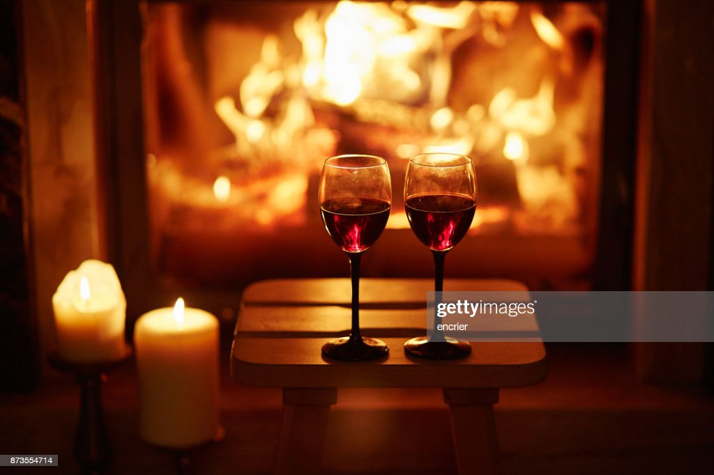 Two glasses of red wine near fireplace : Stock Photo