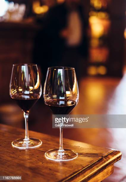 two glasses of red wine on a table - red wine stock pictures, royalty-free photos & images