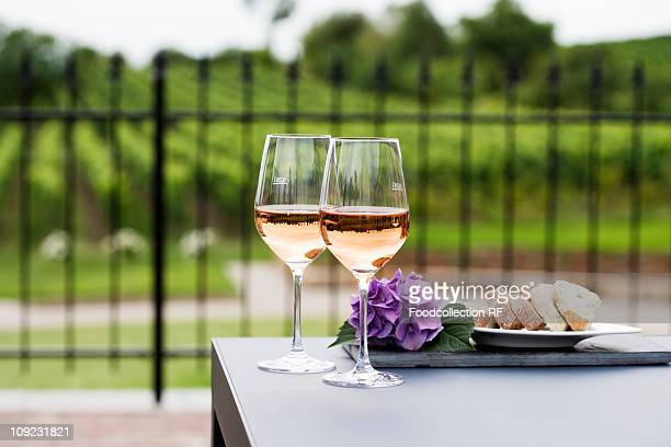 Two glasses of rose wine, vineyard in background