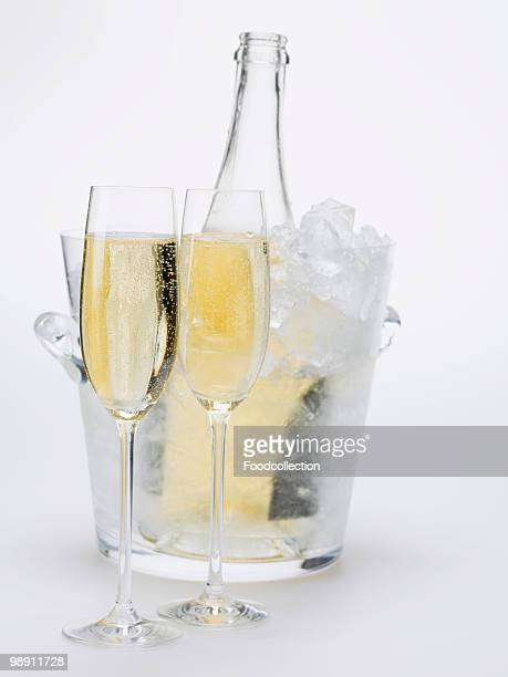 Two glasses of sparkling wine, wine bottle in ice bucket, close-up