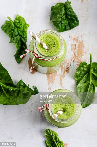 Two glasses of spinach smoothie and spinach leaves on white wood
