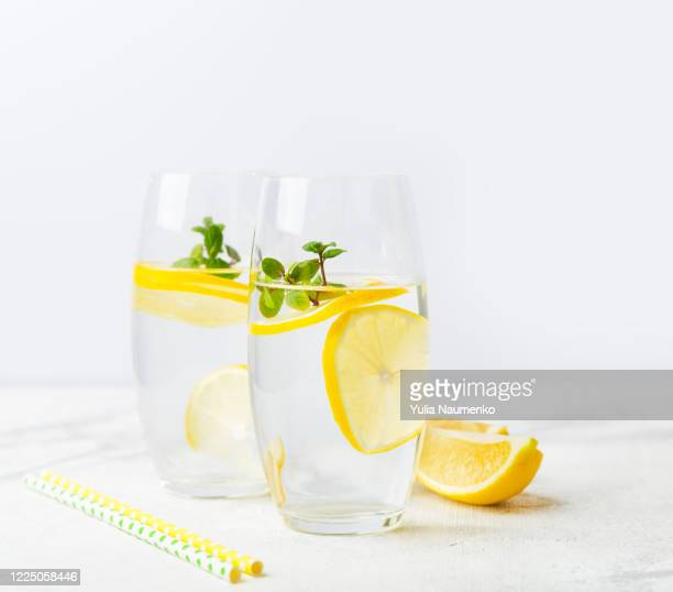 two glasses of water with lemon, homemade refreshing lemonade with slices of organic ripe lemon. the concept of a healthy lifestyle, the right start to the day, a charge of vivacity. copy space. - infused stock pictures, royalty-free photos & images