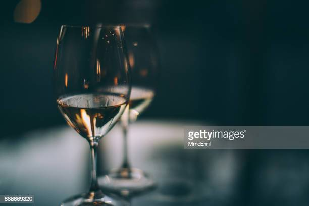 two glasses of white wine on a table - bibita foto e immagini stock