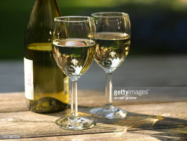 Zwei Gläser Weißwein mit Flasche auf Tisch im Freien
